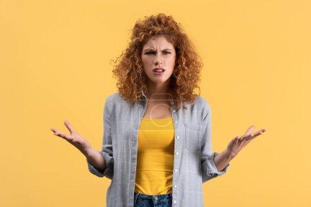 Photo pour Fille rousse inquiète avec geste d'haussement d'épaules, isolée sur jaune - image libre de droit