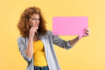 worried woman looking at empty pink speech bubble, isolated on yellow