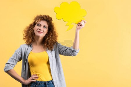 Photo for Pensive smiling woman holding empty speech bubble in shape of cloud, isolated on yellow - Royalty Free Image