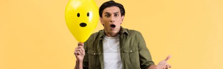 panoramic shot of frightened young man holding shocked balloon, isolated on yellow