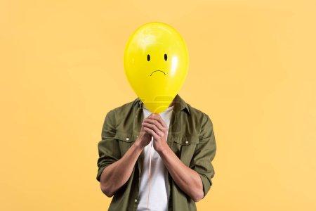 Photo pour Jeune homme tenant triste ballon devant le visage, isolé sur jaune - image libre de droit