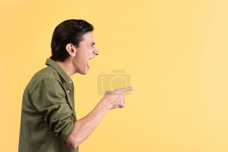 angry young man yelling and pointing isolated on yellow