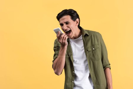 Photo for Angry young man screaming at smartphone, isolated on yellow - Royalty Free Image