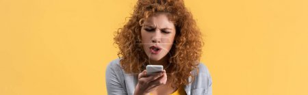 Photo for Panoramic shot of angry redhead woman yelling on smartphone, isolated on yellow - Royalty Free Image