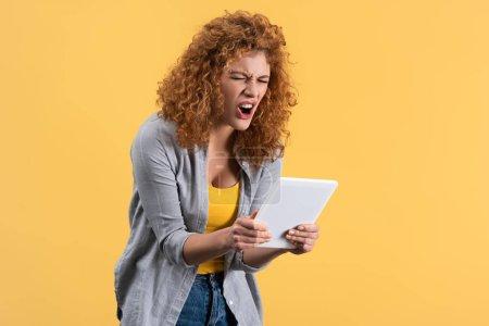 Photo pour Rousse en colère fille criant à tablette numérique, isolé sur jaune - image libre de droit