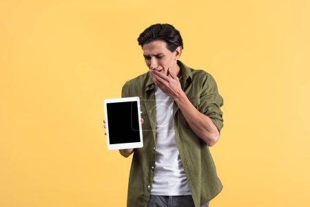 Besorgter Mann zeigt digitales Tablet mit leerem Bildschirm, isoliert auf gelb