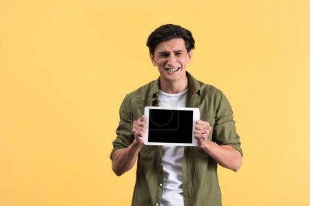 stressed man showing digital tablet with blank screen, isolated on yellow