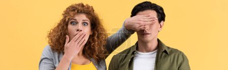 Photo for Panoramic shot of shocked scared girl closing mouth while closing eyes to boyfriend, isolated on yellow - Royalty Free Image