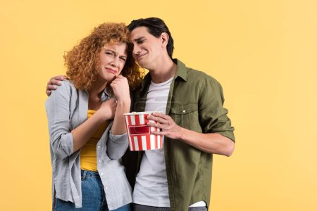 Photo for Upset couple watching drama movie with bucket of popcorn, isolated on yellow - Royalty Free Image