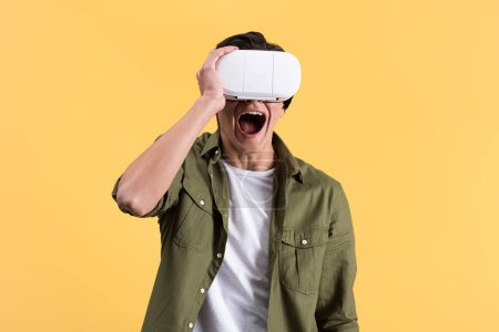Photo for Excited young man yelling while using virtual reality headset, isolated on yellow - Royalty Free Image