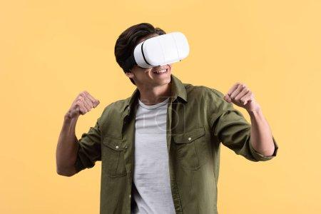 Photo pour Heureux jeune homme tenant les poings et jouant casque de réalité virtuelle, isolé sur jaune - image libre de droit