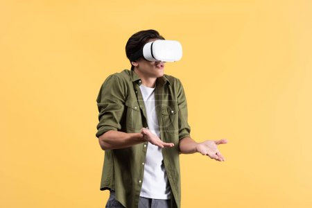 Photo for Irritated young man with shrug gesture using vr headset, isolated on yellow - Royalty Free Image