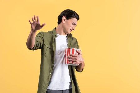Photo pour Irrité jeune homme regarder film avec seau de maïs soufflé, isolé sur jaune - image libre de droit