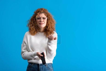 Photo pour Triste fille pleurer, tenant télécommande et regarder la télévision, isolé sur bleu - image libre de droit