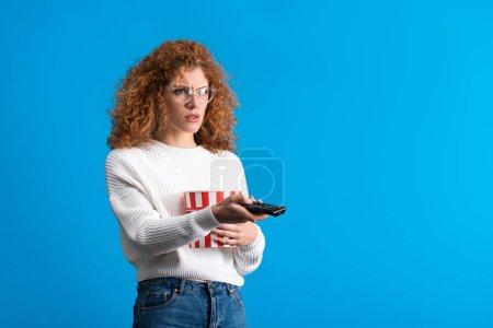 Photo pour Frustré fille regarder la télévision avec télécommande et seau de maïs soufflé, isolé sur bleu - image libre de droit