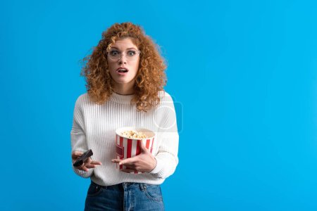 Photo for Shocked girl watching tv with remote control and bucket of popcorn, isolated on blue - Royalty Free Image