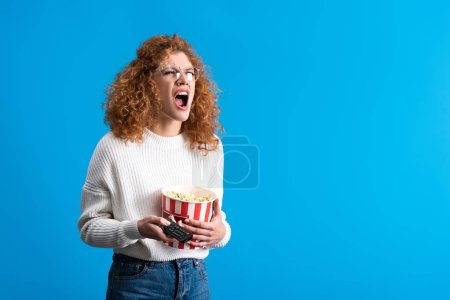 Photo for Angry girl shouting and watching tv with remote control and bucket of popcorn, isolated on blue - Royalty Free Image