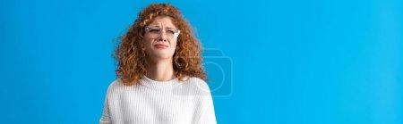 Photo pour Plan panoramique de belle rousse bouleversée fille pleurer isolé sur bleu - image libre de droit