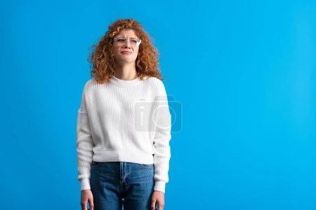 Photo pour Pleurer rousse fille dans des lunettes isolé sur bleu - image libre de droit