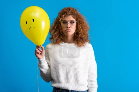 Photo pour Triste fille tenant ballon jaune avec visage bouleversé, isolé sur bleu - image libre de droit