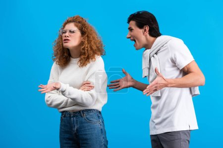 Photo for Angry boyfriend yelling at irritated girlfriend, isolated on blue - Royalty Free Image