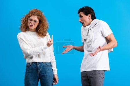 Photo pour Petite amie irritée montrant majeur à petit ami en colère, isolé sur bleu - image libre de droit