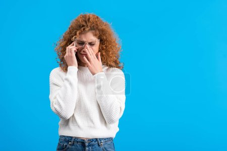Photo for Crying redhead woman in eyeglasses talking on smartphone, isolated on blue - Royalty Free Image