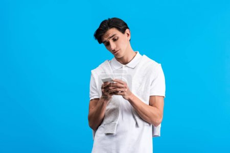 Photo for Skeptical young man using smartphone, isolated on blue - Royalty Free Image