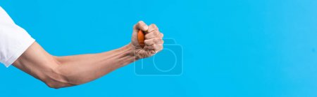 Photo for Panoramic shot of irritated man squeezing stress ball in hand, isolated on blue - Royalty Free Image