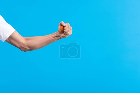 Photo for Cropped view of angry man squeezing stress ball, isolated on blue - Royalty Free Image