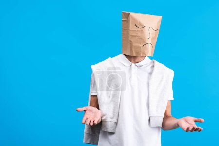 Photo for Skeptical man with sad paper bag on head, isolated on blue - Royalty Free Image