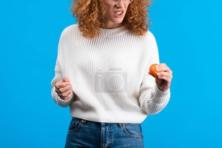 Photo for Cropped view of angry girl squeezing stress ball, isolated on blue - Royalty Free Image