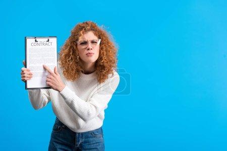 Photo pour Fille irritée pointant vers le presse-papiers avec contrat, isolée sur bleu - image libre de droit