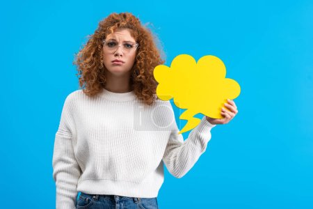 Photo for Upset woman in eyeglasses holding speech bubble in shape of cloud, isolated on blue - Royalty Free Image