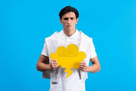Photo pour Homme irrité tenant un nuage jaune parler bulle, isolé en bleu - image libre de droit