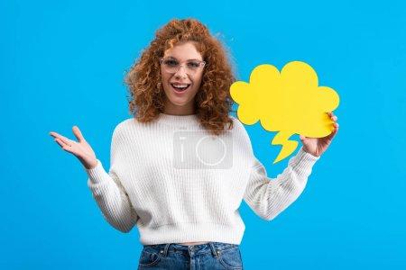 Foto de Mujer emocionada en los ojos sosteniendo burbuja de habla vacía en forma de nube, aislada en azul. - Imagen libre de derechos