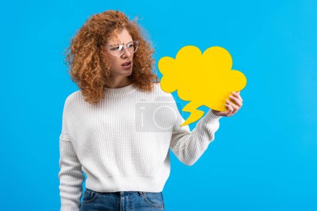 Photo for Skeptical woman in eyeglasses looking at empty speech bubble in shape of cloud, isolated on blue - Royalty Free Image