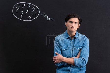 Photo for Pensive young man with question marks in thought bubble on blackboard - Royalty Free Image
