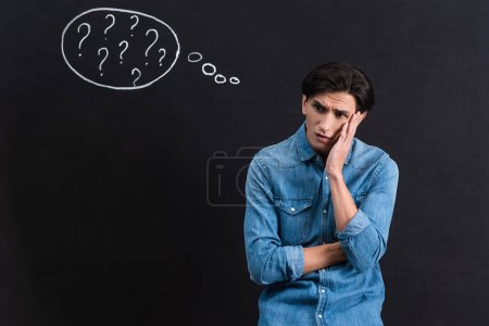 Photo for Worried young man with question marks in thought bubble on blackboard - Royalty Free Image