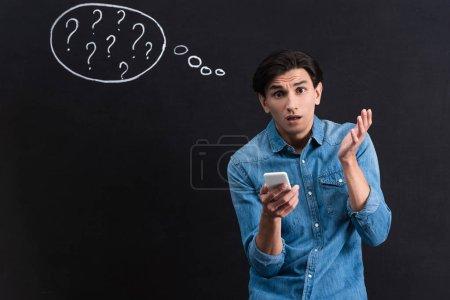 Photo pour Choqué jeune homme à l'aide d'un smartphone, avec des points d'interrogation dans la bulle de pensée dessin sur tableau noir - image libre de droit