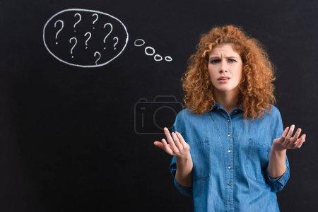 Photo pour Une rousse irritée avec des points d'interrogation dans une bulle de pensée au tableau noir - image libre de droit