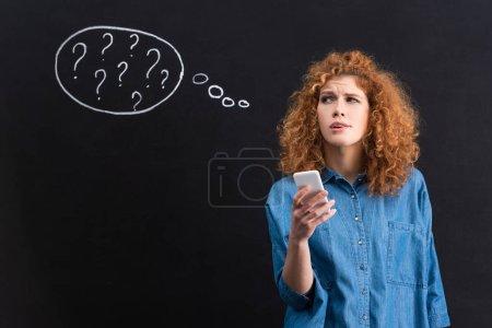 Photo pour Attrayant femme réfléchie en utilisant smartphone, points d'interrogation dans la bulle de pensée sur tableau noir derrière - image libre de droit