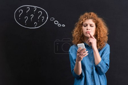 Photo for Pensive woman using smartphone, question marks in thought bubble on blackboard behind - Royalty Free Image
