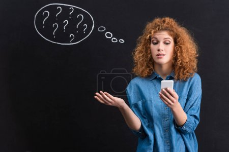 Photo for Skeptical woman using smartphone, question marks in thought bubble on blackboard behind - Royalty Free Image