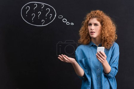 Photo for Skeptical girl using smartphone, question marks in thought bubble on blackboard behind - Royalty Free Image