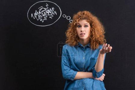 Photo pour Jeune femme à tête rouge sceptique avec une bulle de pensée au crayon - image libre de droit