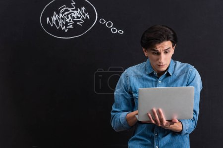 Photo for Emotional man using laptop, with steam from ears drawing on blackboard - Royalty Free Image