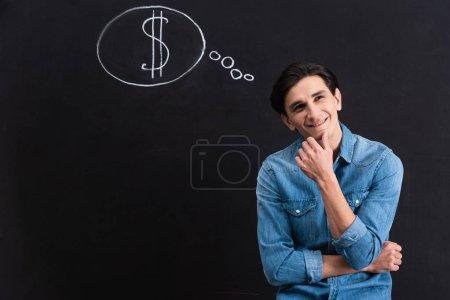 Photo pour Jeune homme rêveur avec un dollar en signe de bulle sur le tableau - image libre de droit