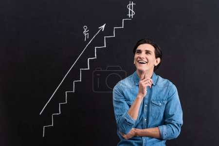 Photo for Cheerful pensive man with startup drawing on blackboard - Royalty Free Image