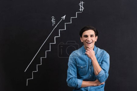Photo for Happy pensive man with business growth drawing on blackboard - Royalty Free Image